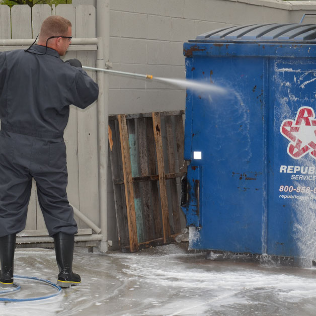 HOODZ technician performing dumpster cleaning service with a pressure washer
