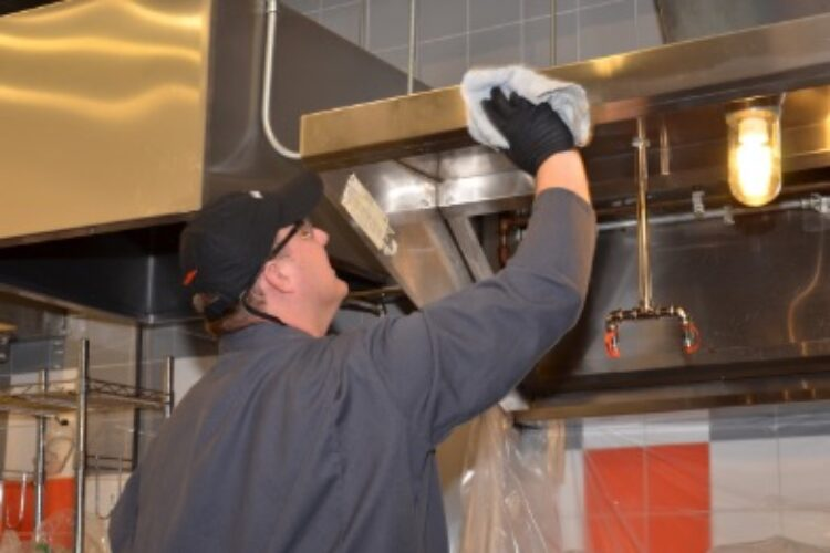 HOODZ technician polishing kitchen exhaust hood