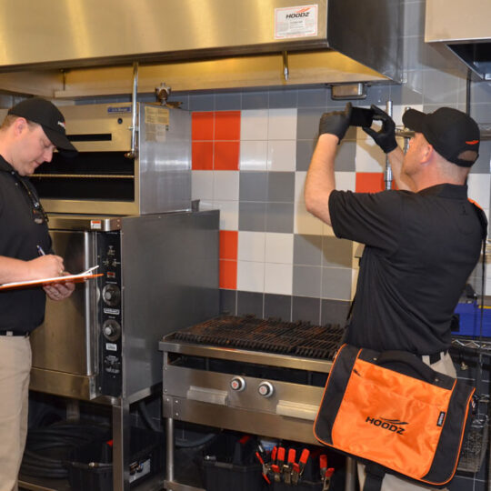 HOODZ technician performing a conveyor oven cleaning service