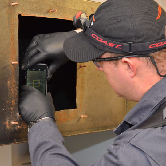 HOODZ tech inspecting an exhaust vent with his phone