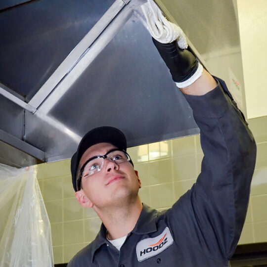 HOODZ service technician cleaning a kitchen exhaust hood