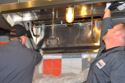 Technician wiping a kitchen hood clean