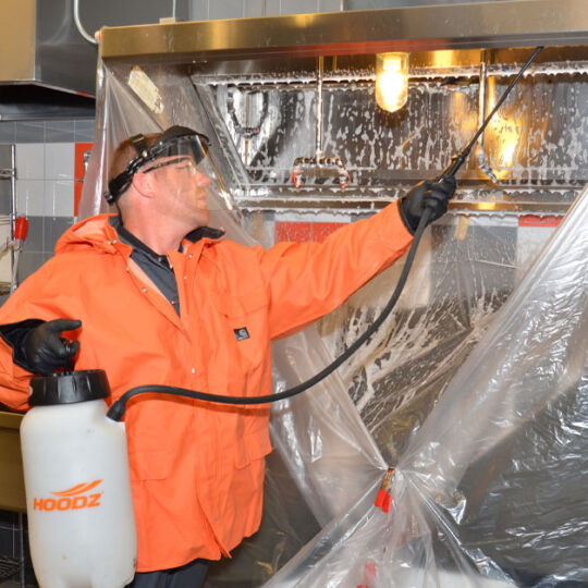 Technician spraying cleaning solution on kitchen exhaust hood