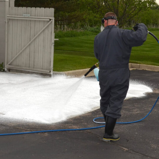 Tech cleaning concrete with a power washer