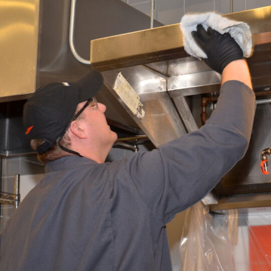 Technician wiping a commercial kitchen hood clean with a towel